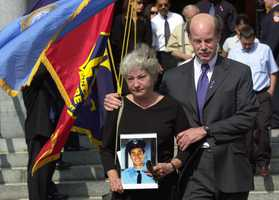 Gricel Zayas-Moyer, left, leaves Mission Church with her husband, Dr. Peter Moyer, after a prayer service for their son, firefighter Manuel DelValle, in Boston Wednesday, Sept. 19, 2001. DelValle, a firefighter with FDNY, Engine Co. #5 in lower Manhattan, was last seen on the 10th floor of the World Trade Center assisting a fellow firefighter who had developed chest pains.