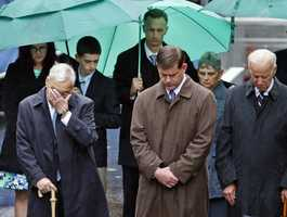 Former Boston Mayor Thomas Menino, left, Boston Mayor Marty Walsh, center, and Vice President Joe Biden bow their heads along with the family of Boston Marathon bombing victim Martin Richard, behind, during a remembrance ceremony at the finish line on Boylston Street in Boston, Tuesday, April 15, 2014.