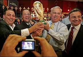 From left, Nick Varano, owner of Strega Ristorante, Senate president Robert E. Travaglini, Mayor Thomas M. Menino, and City Councilor Sal LaMattina hold Italy's World Cup trophy in the North End in 2006.