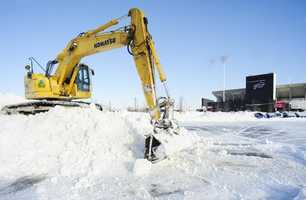 "Work crews move snow in the parking lots outside Ralph Wilson Stadium in Orchard Park, N.Y. Friday, Nov. 21, 2014. Snowed out in Buffalo, the Bills are heading to Detroit to play their ""home"" NFL football game against the New York Jets on Monday night, Nov. 24, 2014."