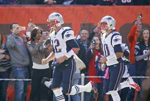 New England Patriots quarterback Tom Brady (12) runs onto the field in front of quarterback Jimmy Garoppolo (10) for warmups before an NFL football game against the Cleveland Browns Sunday, Oct. 9, 2016, in Cleveland.