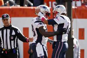 New England Patriots tight end Martellus Bennett, center, hugs quarterback Tom Brady after they connected on a touchdown against the Cleveland Browns in the first half of an NFL football game Sunday, Oct. 9, 2016, in Cleveland.