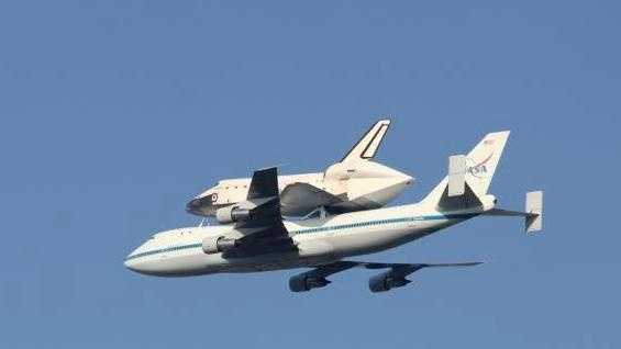 """A piggybacked """"Endeavour"""" makes a low pass over Slidell on its journey to California."""