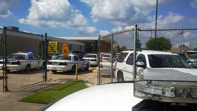 Squad cars from the Jefferson Parish Sheriff's Office are parked outside as deputies work to restore order at Higgins High School.