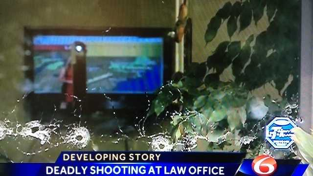 A bullet-riddled door shows some of the dozens of gunshots fired into a Covington law office.