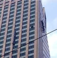 A platform dangles from the Capital One building after it failed during a window washing assignment.