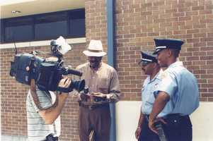 mid-1990s: Norman Robinson giving a Making A Difference Award to two New Orleans Police Department officers in the Second District.