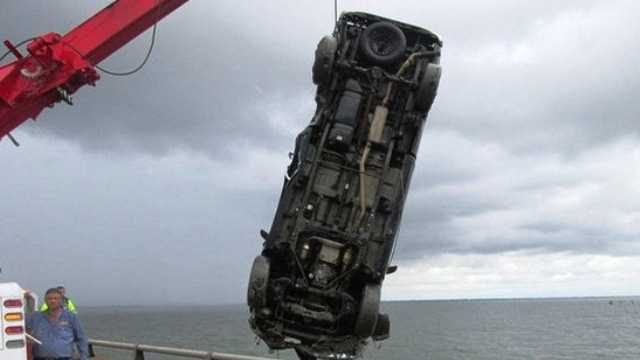 A vehicle is removed from Lake Pontchartrain after crashing over the protective railing on the Causeway on May 31, 2014