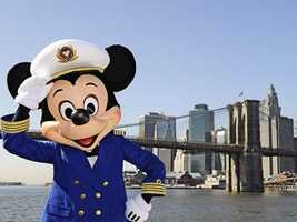 In his signature white sailor's cap and a blue blazer, Mickey poses in front of the Brooklyn Bridge on board one of the Disney cruise ships.