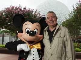 Mickey, wearing his signature yellow bow tie, welcomes journalist Dan Rather to Epcot.
