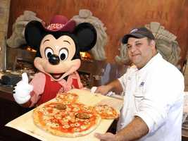 Mickey gets into the spirit of Italy as he helps prepare a pizza at Via Napoli.