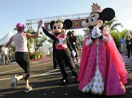 Mickey matches Minnie's pink princess dress with a pink tie and cummerbund at the Princess Run.