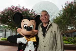 Journalist and TV anchor Dan Rather poses with Mickey Mouse Aug. 16, 2009 at Epcot in Lake Buena Vista, Fla. Rather was on vacation at the Walt Disney World theme park.