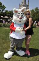 "Ke$ha poses at the Magic Kingdom with The White Rabbit, from Disney's ""Alice in Wonderland"" -- and his watch which always reminded him he was ""late, for a very important date.""  Ke$ha's debut single, which hit #1 in multiple countries, was entitled ""Tik Tok."""