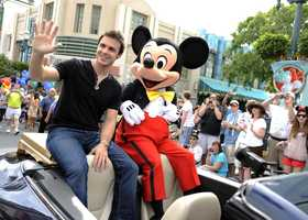 "Joined by Mickey Mouse, ""American Idol"" season eight winner Kris Allen waves to fans May 29, 2009 during a celebratory parade through Disney's Hollywood Studios in Lake Buena Vista, Fla."