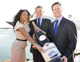 "Oscar-winning actress and Grammy Award-winning singer Jennifer Hudson (left) poses Jan. 19, 2011 at Port Canaveral, Fla. with Walt Disney Company president and CEO Robert A. Iger (middle), Walt Disney Parks and Resorts chairman Thomas O. Staggs (right) and a ceremonial bottle of Champagne at the christening ceremony for the new ""Disney Dream"" cruise ship."
