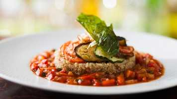 Ratatouille Confit Byaldi - Oven-baked Zucchini, Eggplant, Mushrooms, and Caramelized Onions sliced and layered on Quinoa served with Bell Pepper Salsa