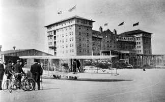 1912: An airplane sits on the beach with the Clarendon Hotel in the background.