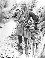 Seminole Indian Chief Tallahassee poses wearing a finger-woven sash and garters. His trade cloth leggings have beadwork at the ankles. He is wearing a beaded shoulder pouch and appliquework adorns his coat (long shirt).