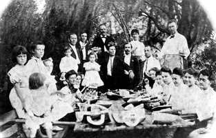 A group of people eat watermelon at a picnic during the 1800s in Lake City.