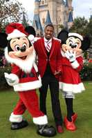 "Actor Nick Cannon points to his red sparkling holiday shoes as he poses with Mickey Mouse and Minnie Mouse while taping the ""Disney Parks Christmas Day Parade"" TV special in the Magic Kingdom park at Walt Disney World in Lake Buena Vista, Fla.  Cannon is one of the hosts for the holiday special."