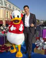 "Mario Lopez hangs out with Donald Duck during the taping of the ""2012 Disney Parks Christmas Day Parade"" holiday television special at Disneyland in Anaheim, Calif."