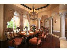 This formal dining room is 18 feet by 14 feet and exemplifies elegance with grand windows, marble columns and exquisite chandelier.
