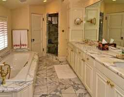 Marble is showcased throughout the master bathroom which includes an inviting spa tub, separate shower and dual sinks.