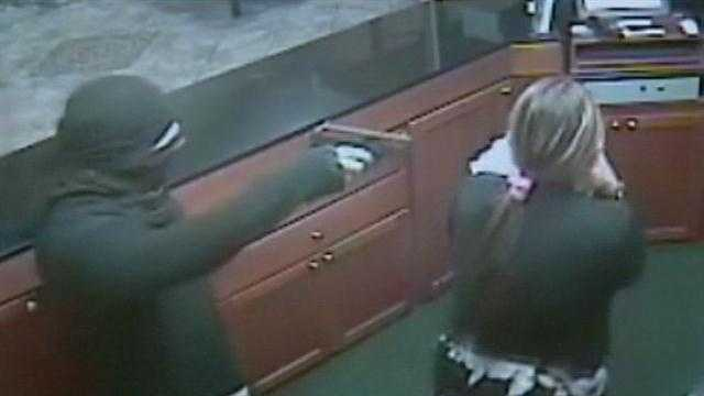 Surveillance video from a hotel robbery shows a man pointing his gun at an unarmed woman and her child.