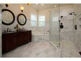 This master bathroom is one of six bathrooms in the home. It features an exquisite marble shower and huge spa tub.