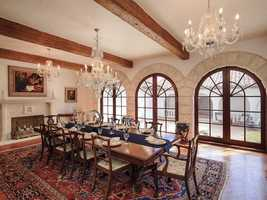A dramatic formal dining room with adjacent wet bar boasts a wood and gas-burning fireplace and Palladian French doors leading to a courtyard.