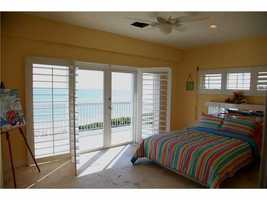 This guest bedroom features a spacious balcony overlooking the ocean blue.