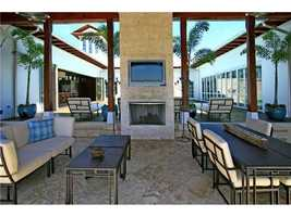 An outdoor dining space features a fireplace and a television for entertainment.