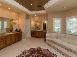Master bathroom features a gracious spa tub and two vanities.