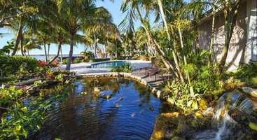 The island features a Spanish-style estate with a private guest wing and tennis court.