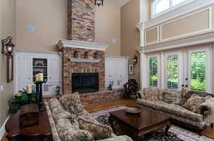 Traditional, brick fireplace is the focal piece in this formal living room.
