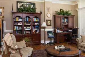 Large personal study has beautiful wooden floors, desk, and bookcases.