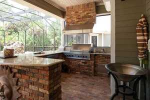 Full serving summer kitchen perfect for grilling and entertaining by the pool.