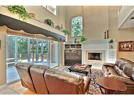 Reclining sofas surround a beautiful fireplace and big screen TV in this relaxing living room, which opens out onto the patio and features vaulted ceilings.