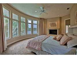 Retreat to this beautiful master bedroom which features a marble fireplace and bay windows overlooking the lake.