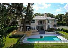 Aerial view from behind the home showcases the pool, jacuzzi, porch, and yard.