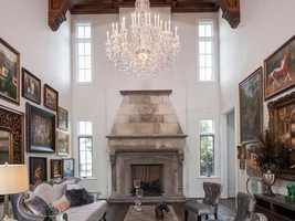 You'll see contrasting old and new elements throughout the home. This formal living room, for instance, utilizes the vaulted ceilings with dramatic wooden panels, a beautiful chandelier, and a stone fireplace with olde world details.