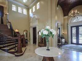 An elegant stairway welcomes owners and guests at the front door.