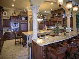 The gourmet kitchen is a chef's dream with large granite island, copper sinks, and built-in Starbucks-like coffee bar.