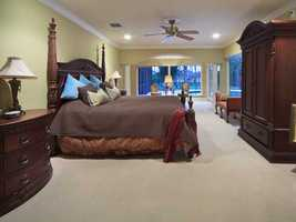 The master bedroom is unbelievable with the size of the space and undisturbed views of the nature of the lake beyond.