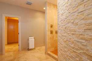 The bathroom is more fitted to be called a spa with travertine flooring, bamboo cabinetry, and a curved Norstone walk-in shower w/ body sprays and rain head.