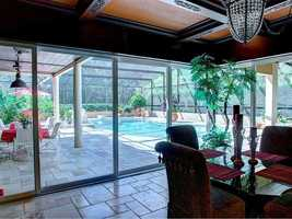 The dining room opens out into an enclosed pool area.