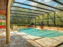 The enclosed pool deck which features an outdoor kitchen complete with sink, breakfast bar seating, granite countertops and built-in gas grill.