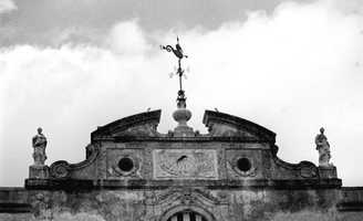 A weather vane on top of one of the mansion's rooftops.  Photograph taken in 1986.