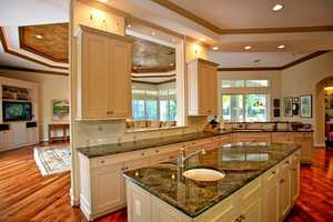 An open-layout kitchen looks out over the family room and welcomes an entertaining atmosphere. It features custom cabinetry and marble-topped counters.